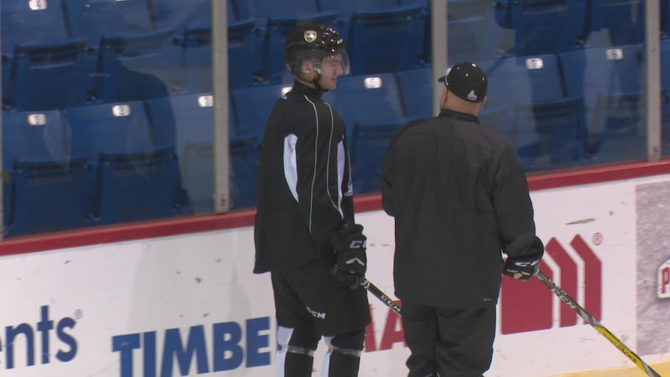 Lukas Cormier et Guy Giurouard, l'entraîneur adjoint des Islanders de Charlottetown, se parlent sur la glace.