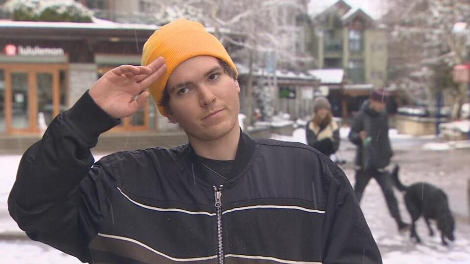 Un jeune homme fait un signe de salut au milieu du village de Whistler.