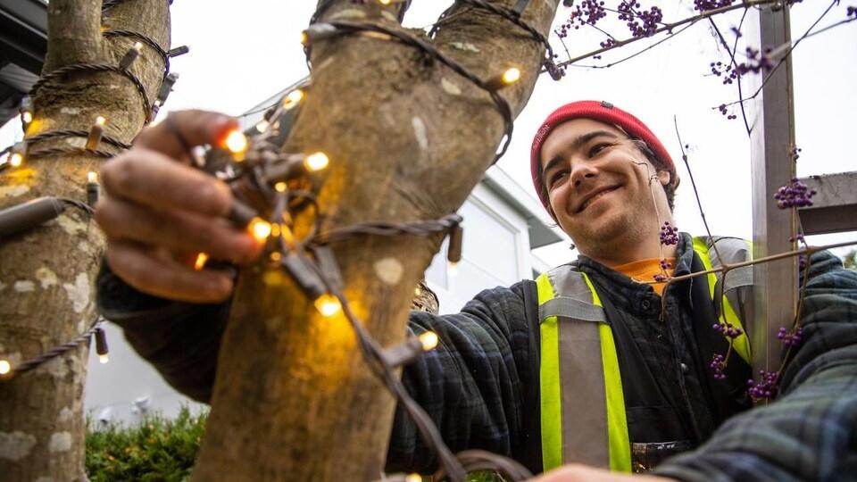 Un homme installe des lumières de Noël sur un arbre.