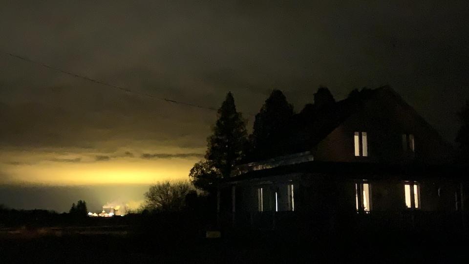 Une maison dans la pénombre et le ciel éclairé au loin.