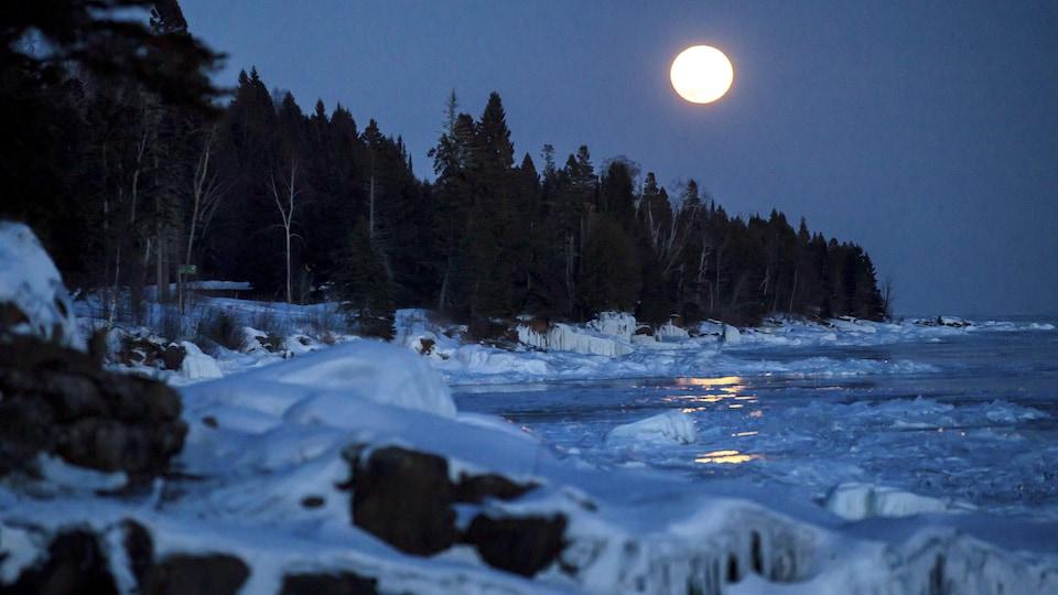 La lune brille sur le lac Supérieur gelé.