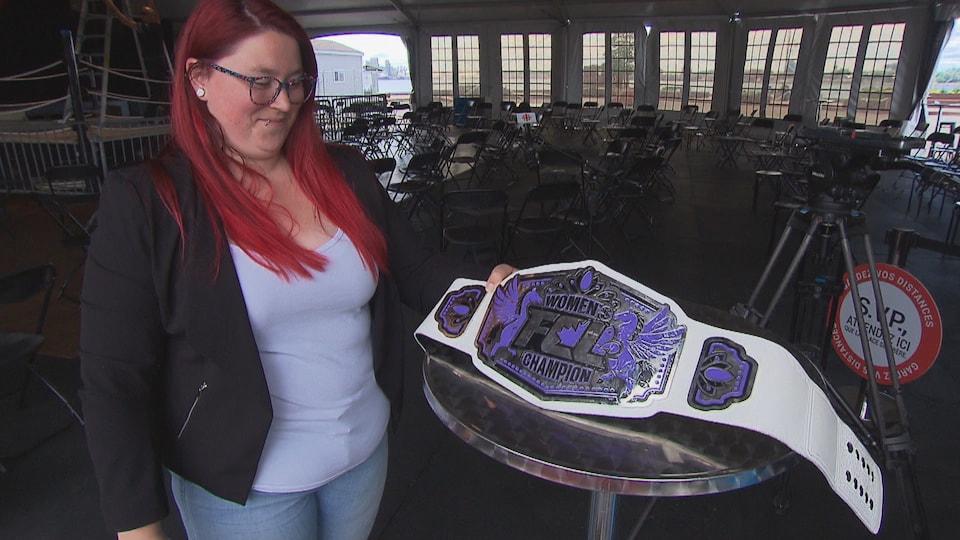 Une femme tient une ceinture de lutte qui est posée sur une table.