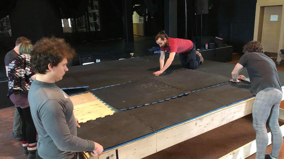 Des gens posent des tapis mous sur une scène en bois.