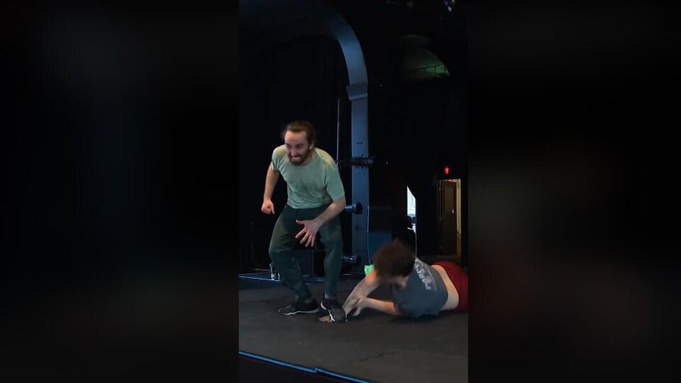 Un homme appuie son pied sur la main d'un autre homme couché par terre.