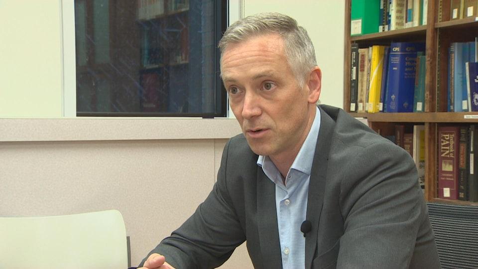Un homme en veston et chemise en entrevue.