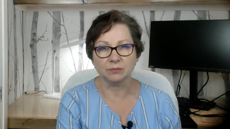 Une femme assise à son bureau qui parle à l'ordinateur.