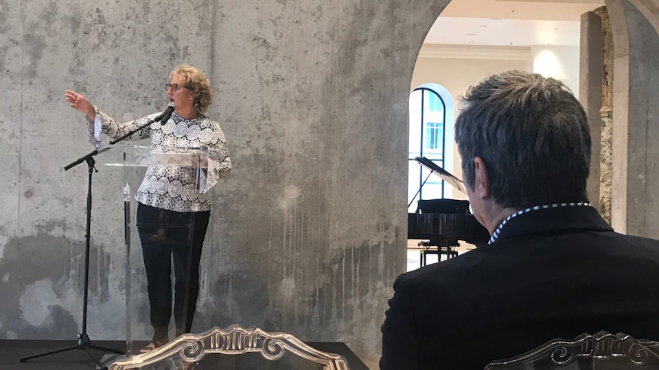 Lynda Beaulieu sur une petite scène parle dans un micro.