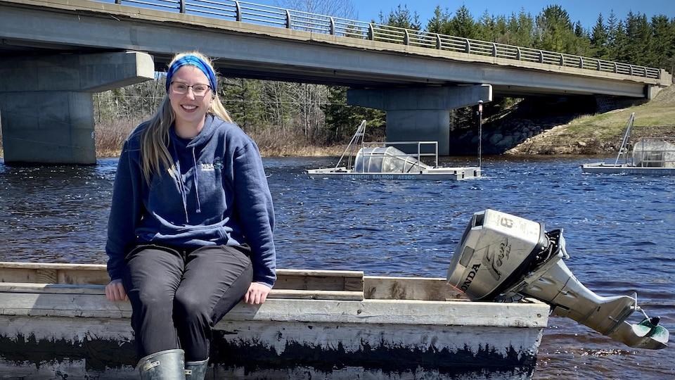 Lyndsay Jay-Keating est assise sur un canot à moteur au bord de la rivière Miramichi. Derrière elle se trouvent deux trappes rotatives qui servent à attraper les saumoneaux.
