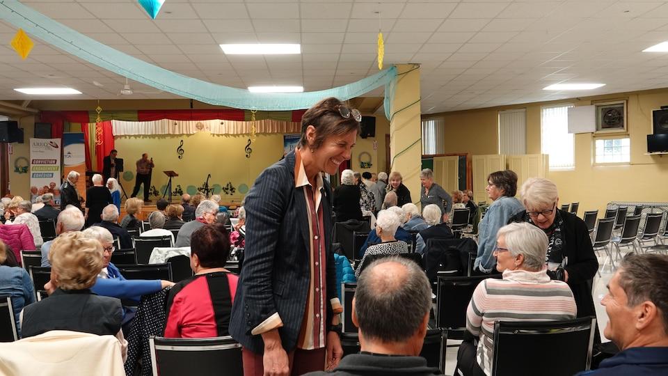 Lyne Bessette discute avec des aînés assis dans une grande salle commune.