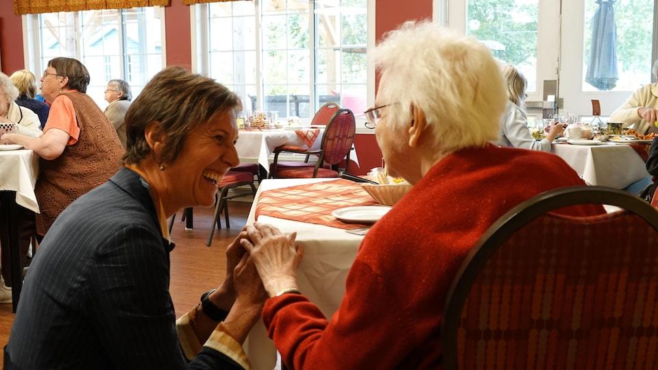 Lyne Bessette discute avec une aînée dans la cafétéria de la résidence.