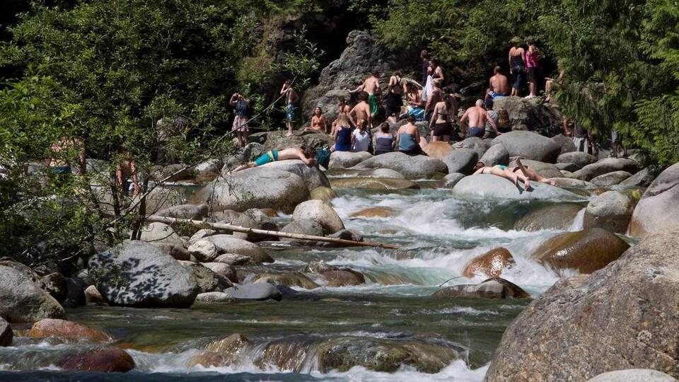 Des baigneurs dont certains couchés et assis sur des roches dans une rivière.