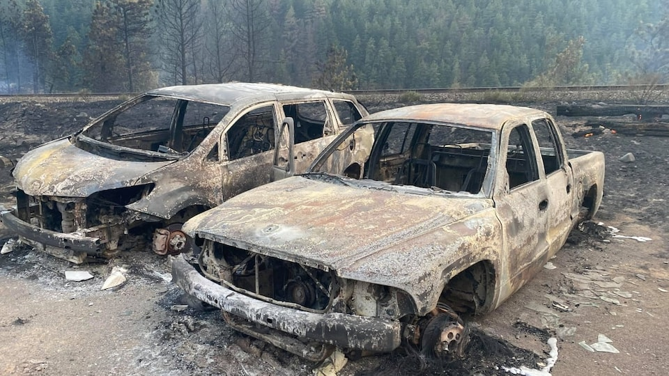 Two cars covered in ashes without windows and tires in a desert environment.