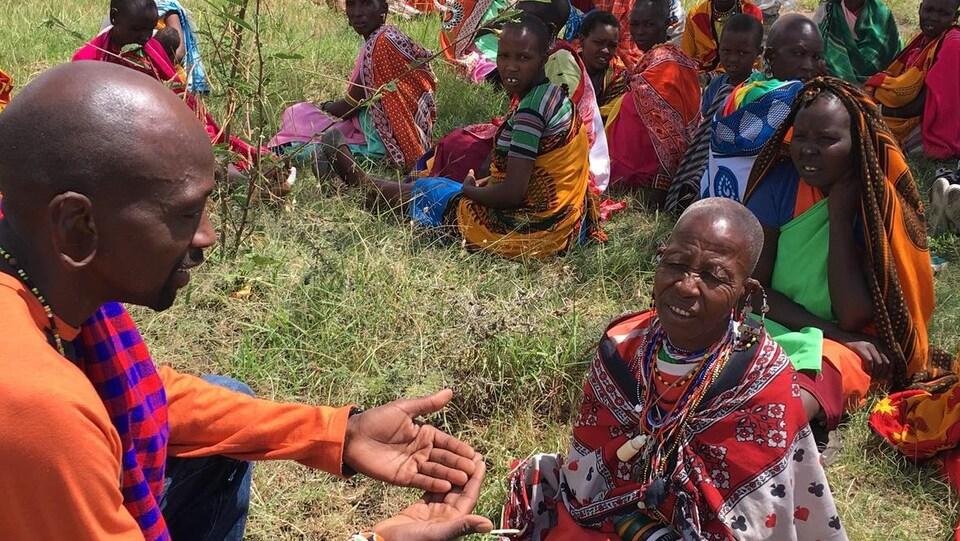 Lialo Saalash devant un groupe de femmes portant des tissus très colorés.