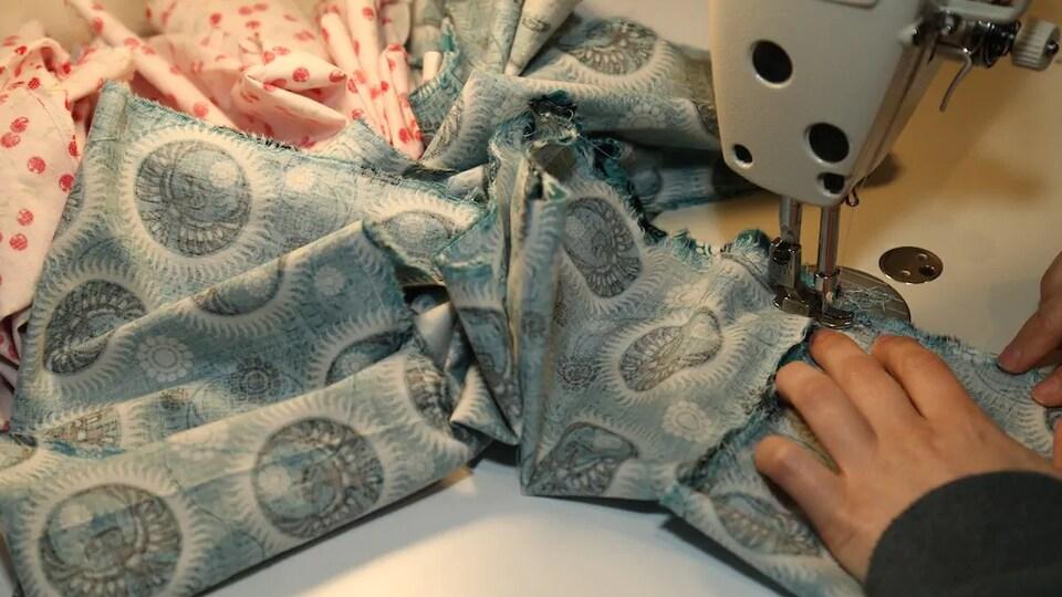 Gros plan sur un morceau de tissu en train d'être cousu dans une machine à coudre.