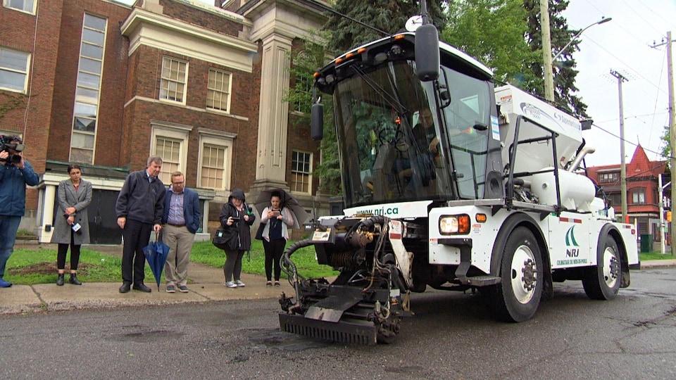 Le Python 5000, conduit par un employé municipal, tasse l'asphalte dans un trou sous le regard du maire Watson et du conseiller Stephen Blais.
