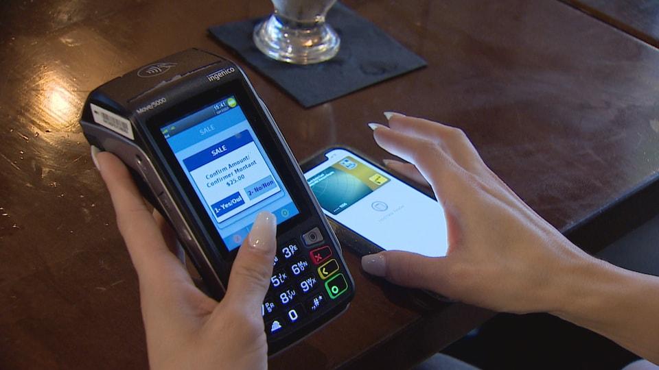 Une machine à carte bancaire avec une application de paiement sur un téléphone intelligent.