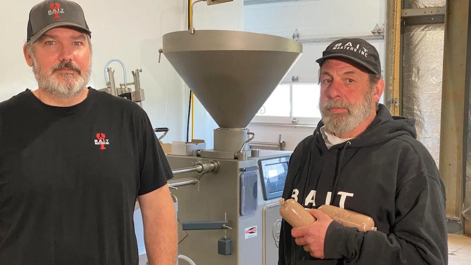 Wally MacPhee et Mark Prevost debout devant l'équipement de production.