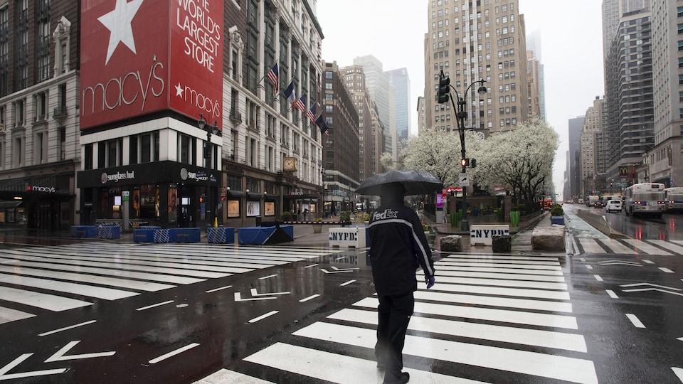 Un homme traverse une rue près du Macy's de New York.