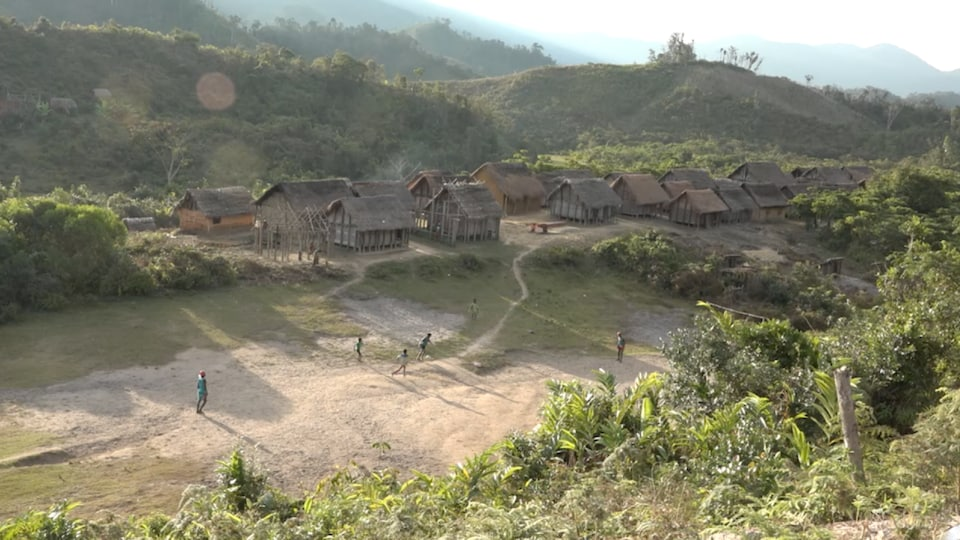 Vue aérienne d'un village de maison en bois et en pailles, construites à même la terre.