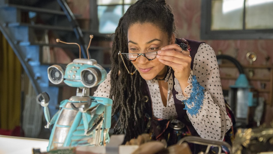 A woman holds her glasses on the tip of her nose while looking at a little blue robot.