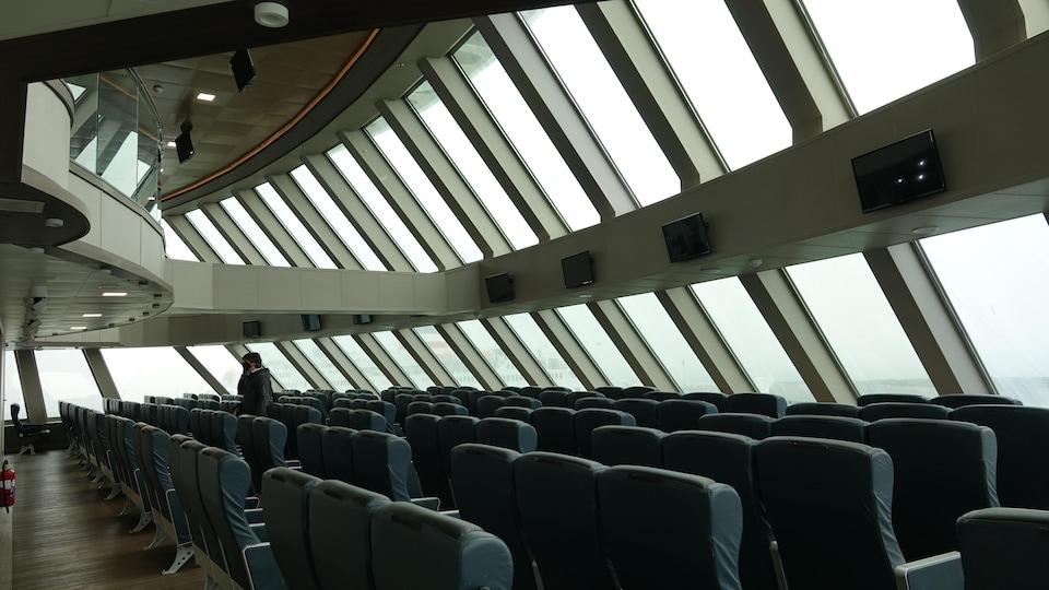 Un salon de passagers surplombé par une mezzanine complètement vitrée.