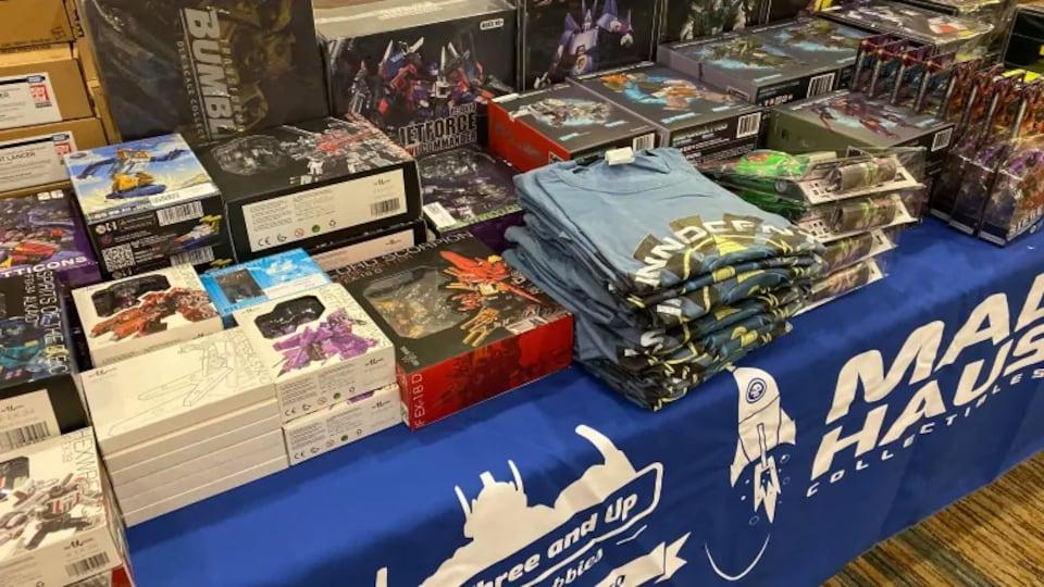 Une table sur laquelle sont disposés des t-shirts et des jeux
