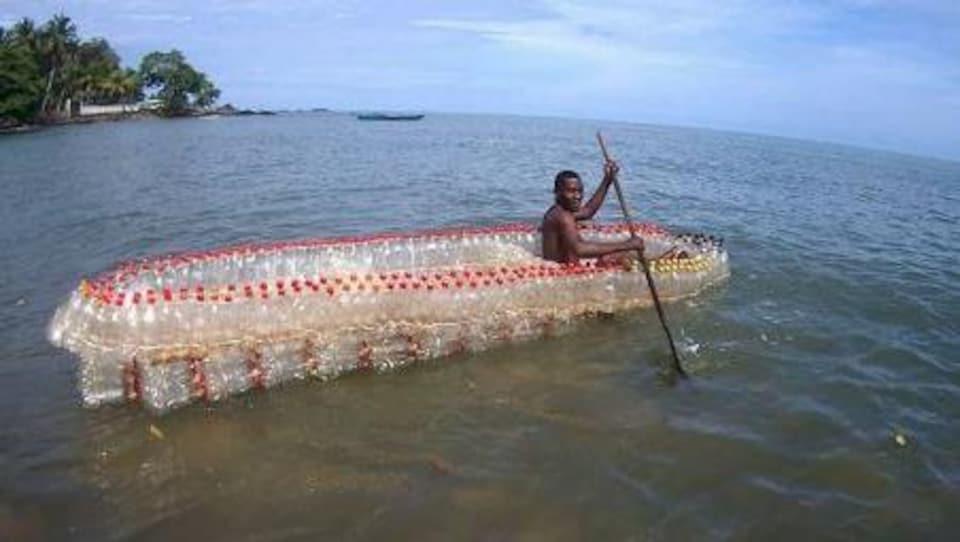 Au Cameroun, à Douala, un jeune homme vogue sur l'un des bateaux qu'il a conçus à partir de bouteilles en plastique recyclé.