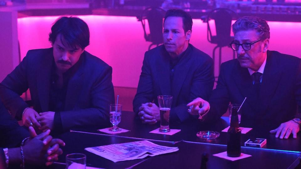 Trois hommes en costume sont dans un bar de nuit.