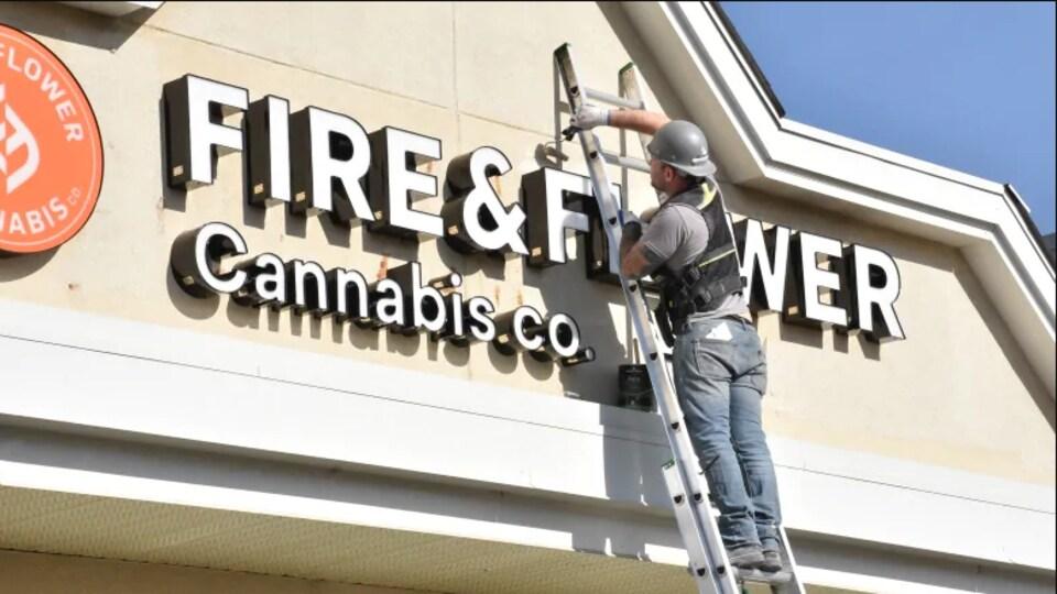 Un travailleur effectue une retouche à l'enseigne de du commerce Fire and Flower.