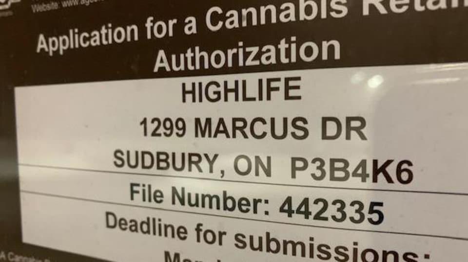 Un écriteau sur lequel on lit des informations sur un magasin de cannabis.