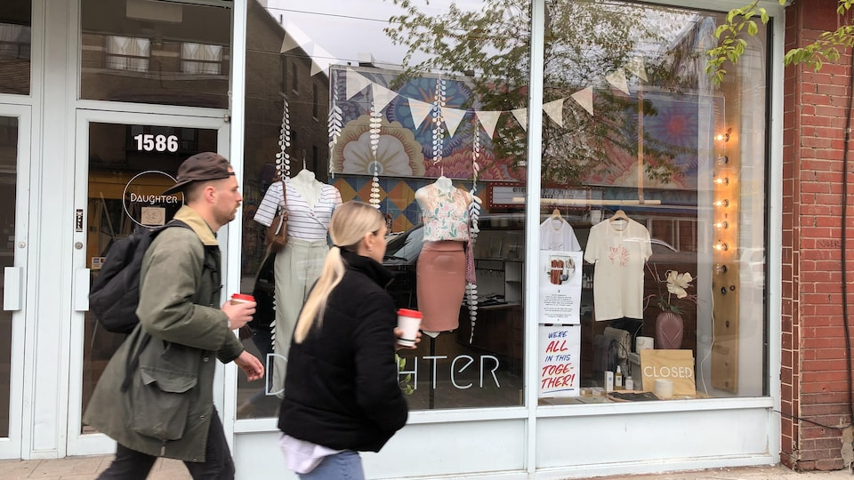 Deux personnes passent devant un magasin de prêt-à-porter, cafés à la main, à Toronto.