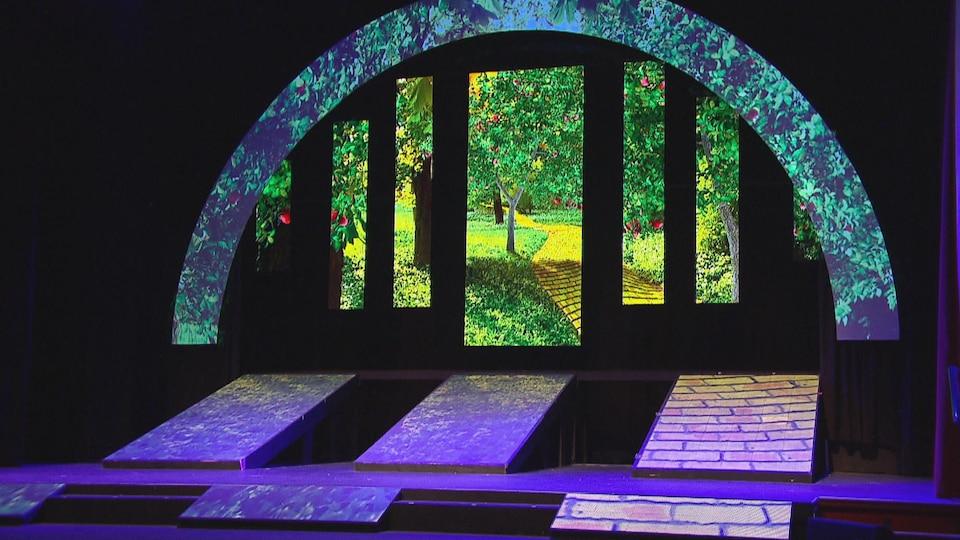 Décor de spectacle évoquant le magicien d'Oz : une forêt enchantée et invitante dans des couleurs néon sur l'estrade d'un théâtre.