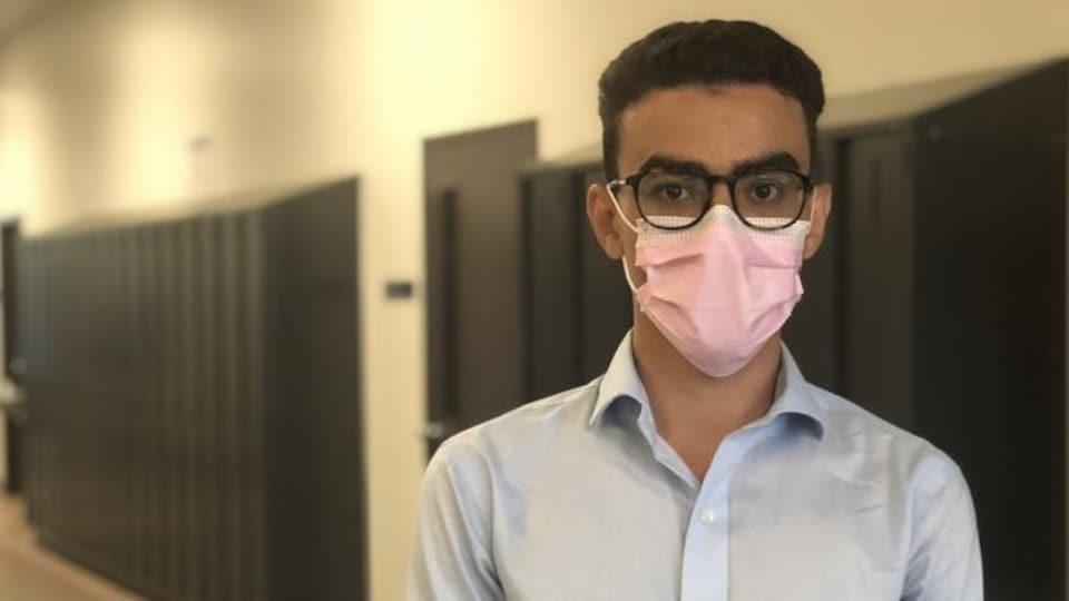 Un homme en entrevue dans le corridor, devant des casiers.