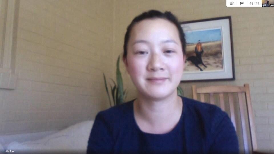 Une femme devant une webcam.