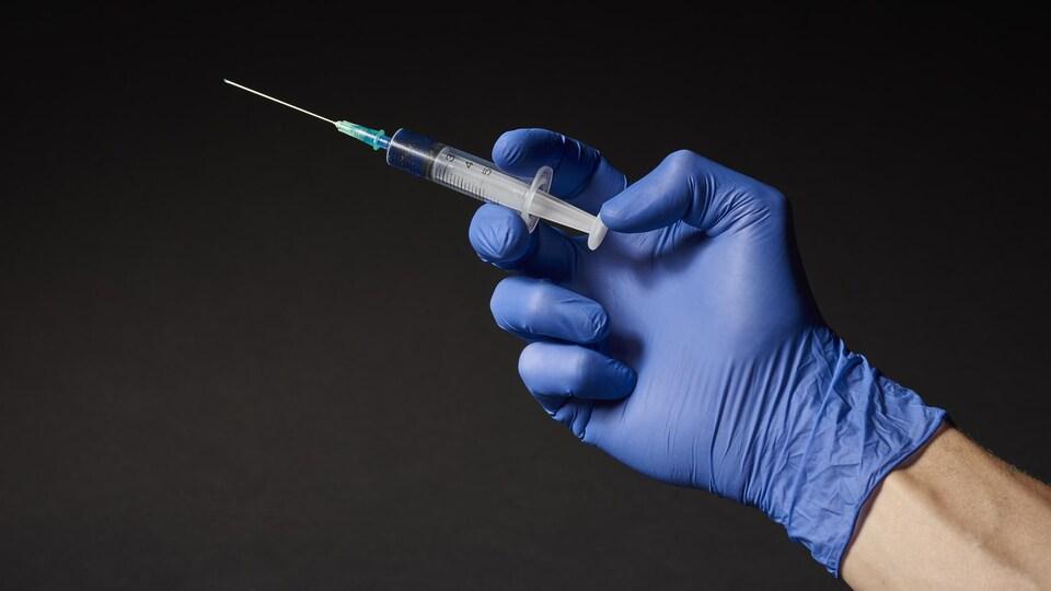 La main d'une personne avec une seringue contenant un vaccin.