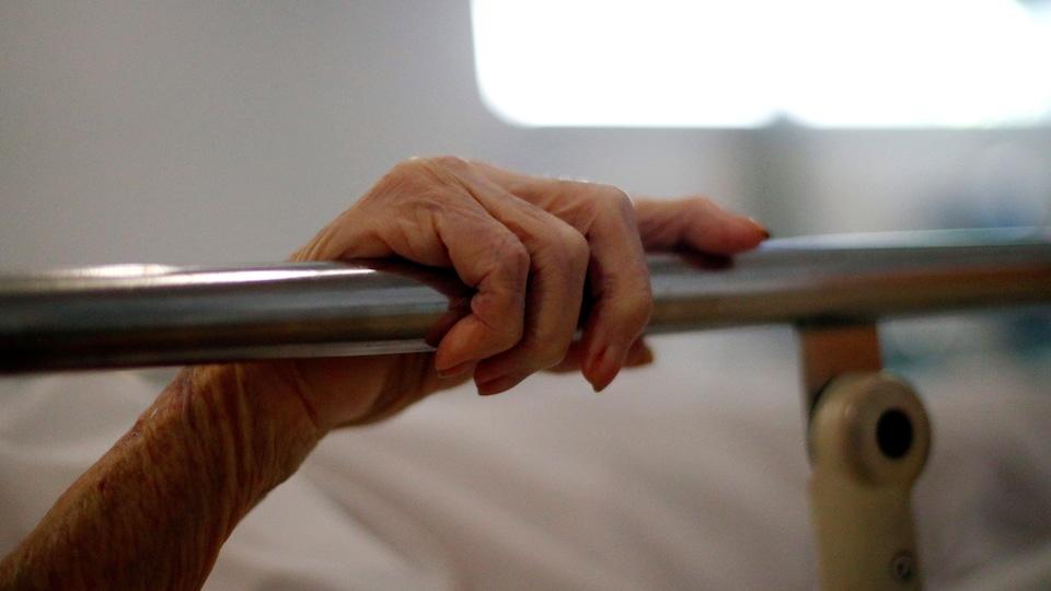 Un patient tient l'une des barres métalliques de son lit d'hôpital.