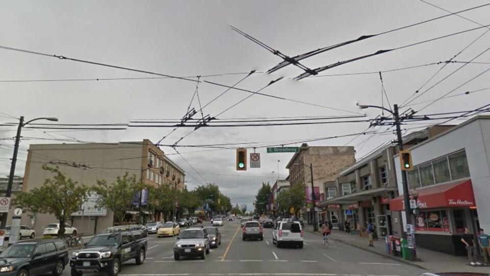 On voit à l'avant-plan les fils électriques pour les autobus, et on a une vue sur la rue, avec des voitures dans les deux sens, un feu de circulation, à l'arrière-plan des immeubles.