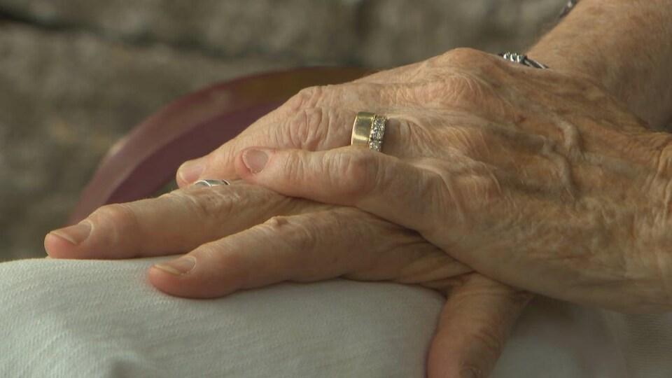 Les mains de deux époux âgés portant leurs alliances sont posées l'une sur l'autre.