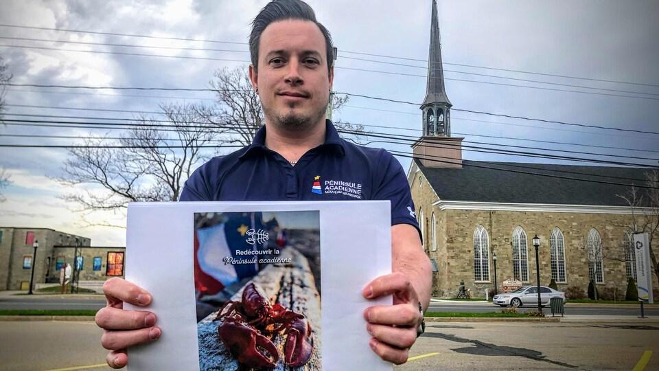 Il tient une affiche illustrée d'un homard devant un drapeau acadien et sur laquelle il est écrit «Redécouvrir la Péninsule acadienne.»