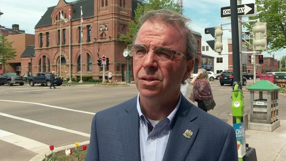 Le maire de Charlottetown, Philip Brown, devant un immeuble brun.