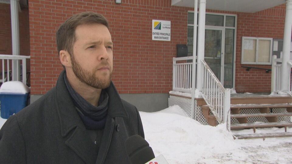 Le maire Guillaume Lamoureux répond aux questions d'un journaliste devant un bâtiment en briques rouges.