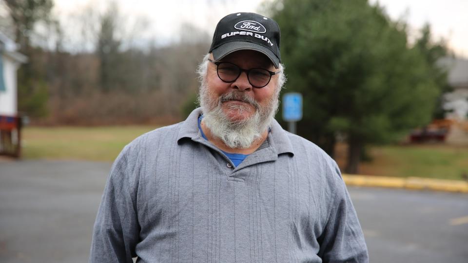 Un homme se laisse prendre en photo, à l'extérieur.