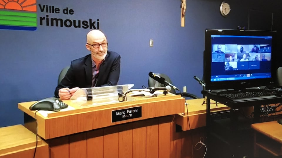 Le maire Marc Parent est seul avec un écran sur lequel on voit chacun des conseillers en visioconférence.