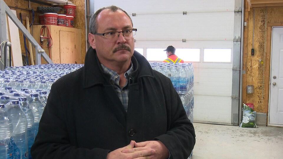 Le maire de St-Mathieu-d'Harricana, Martin Roch, devant des palettes de caisses d'eau embouteillée.