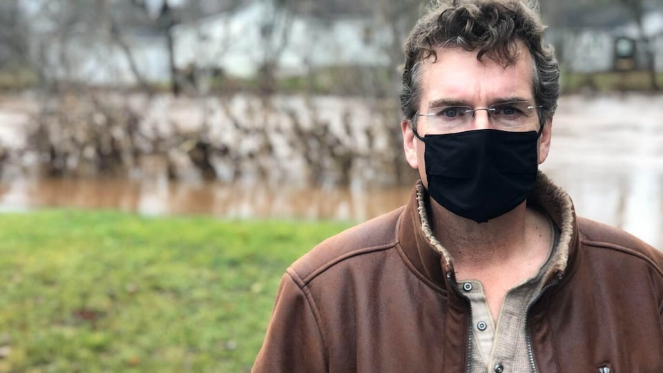 Marc Thorne, le maire de Sussex, devant une rivière. Le maire porte un masque sanitaire.