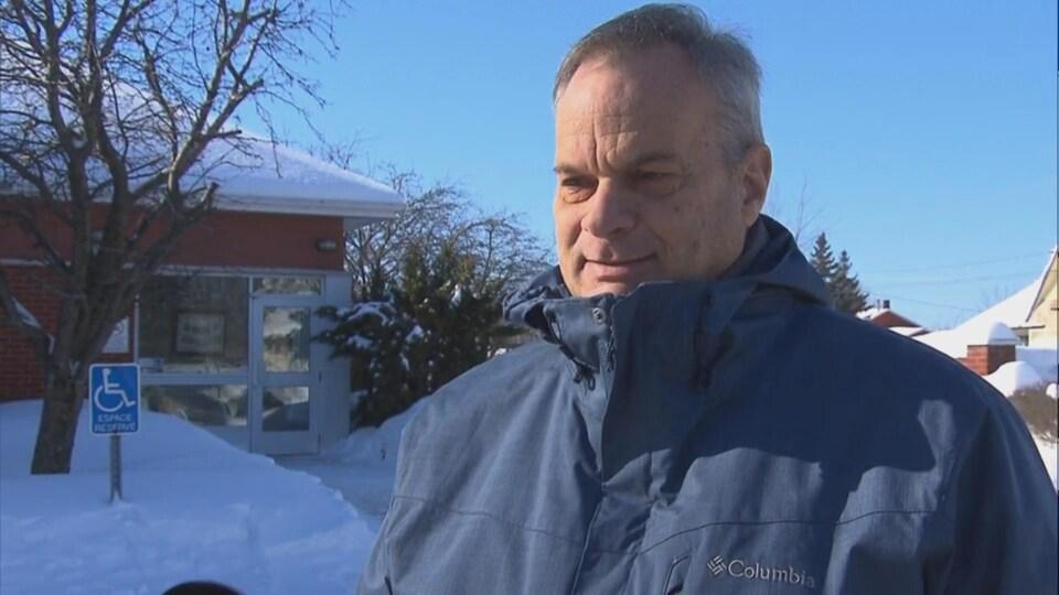 Le maire debout, dehors, près de la mairie en hiver.