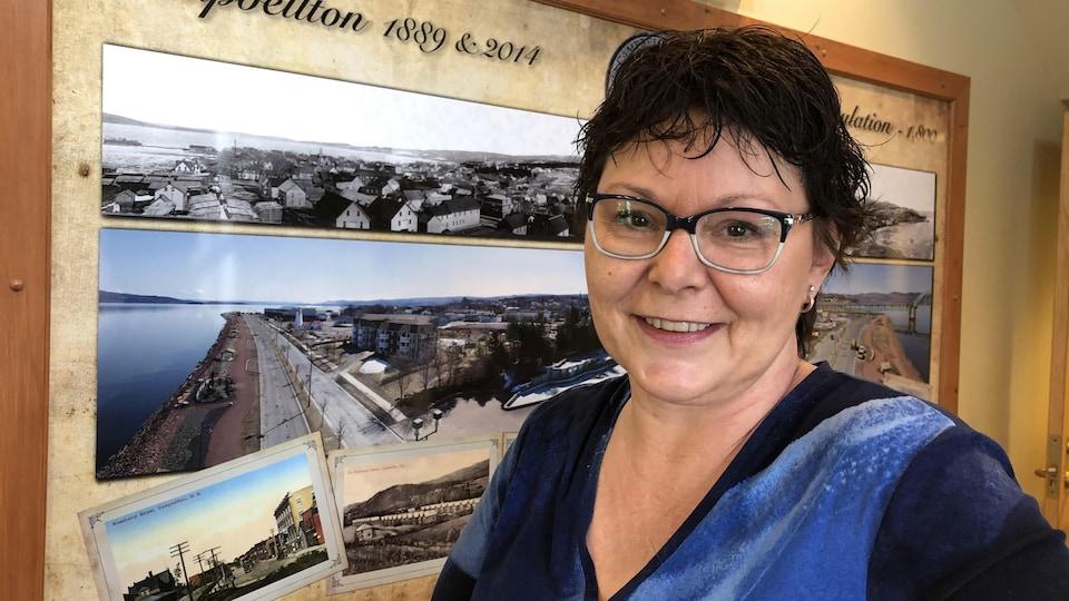 La mairesse de Campbellton, Stephanie Anglehart-Paulin, souriante devant un tableau de Campbellton.