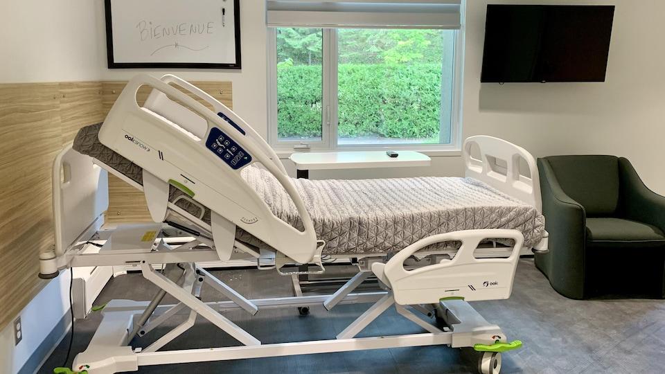 Un lit médical dans une chambre avec télévision et une grande fenêtre.