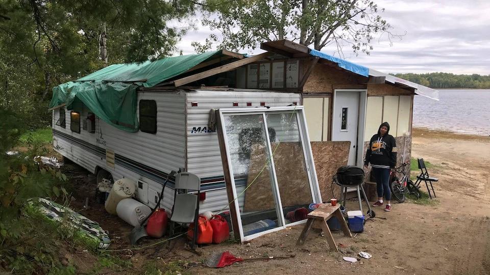 Une maison délabrée sur le bord d'un lac. Elle est faite avec des morceaux de roulotte et de contreplaqué, ainsi que d'une bâche de plastique en guide de toit.