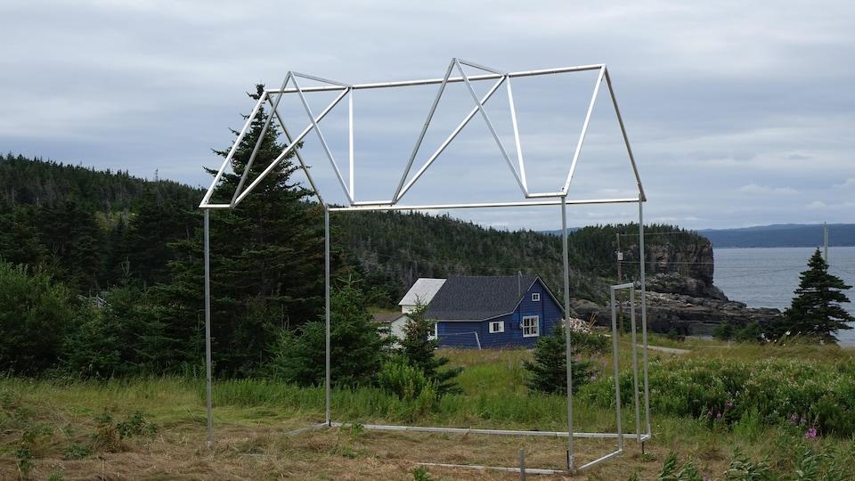 Une sculpture d'une maison construite avec des tubes carrées d'aluminium.